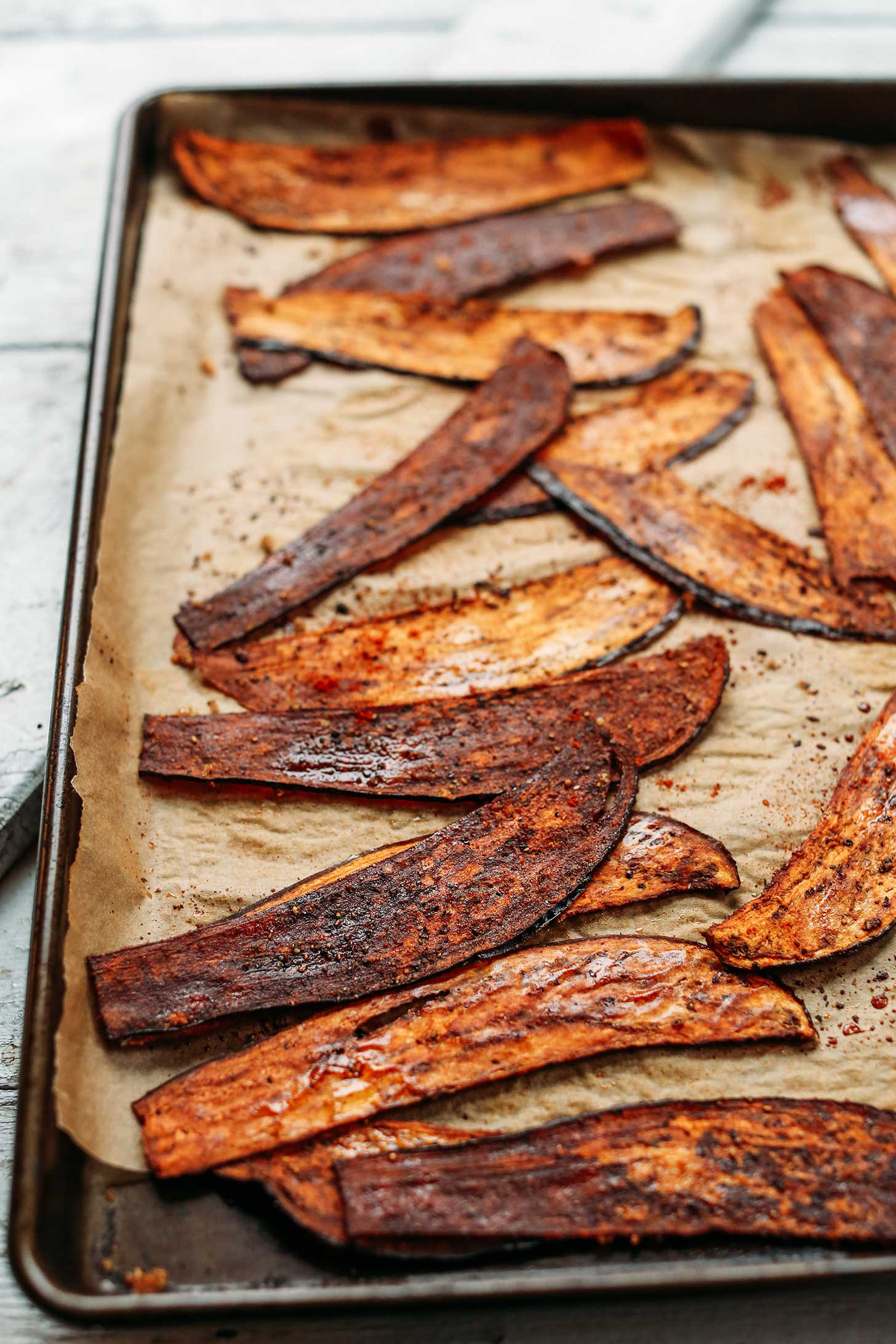 Parchment-lined baking sheet with Crispy Eggplant Bacon slices