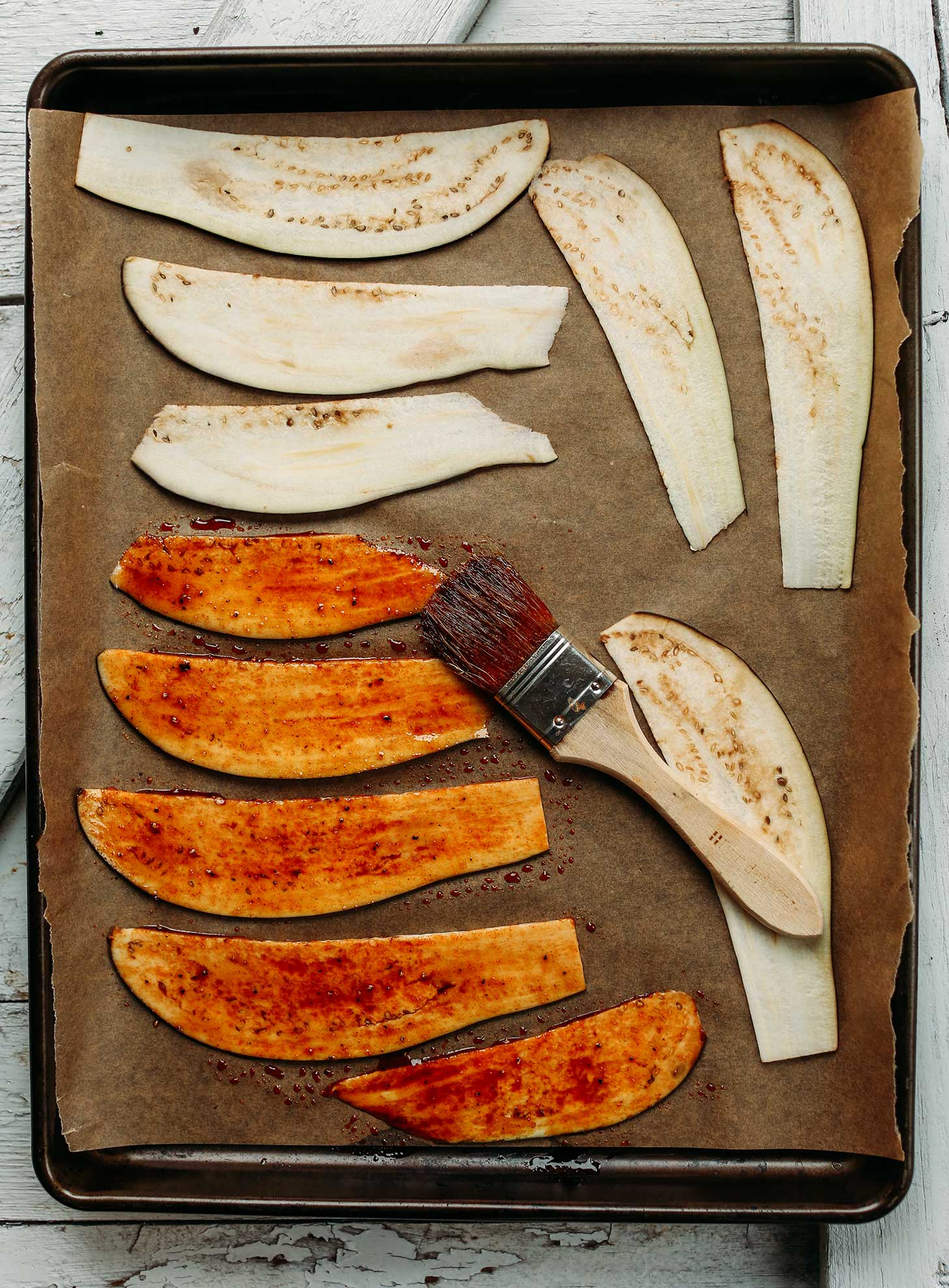 Brushing sauce onto sliced eggplant laying on a parchment-lined baking sheet