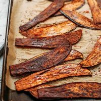 "Slices of Crispy Eggplant ""Bacon"" on a parchment-lined baking sheet"