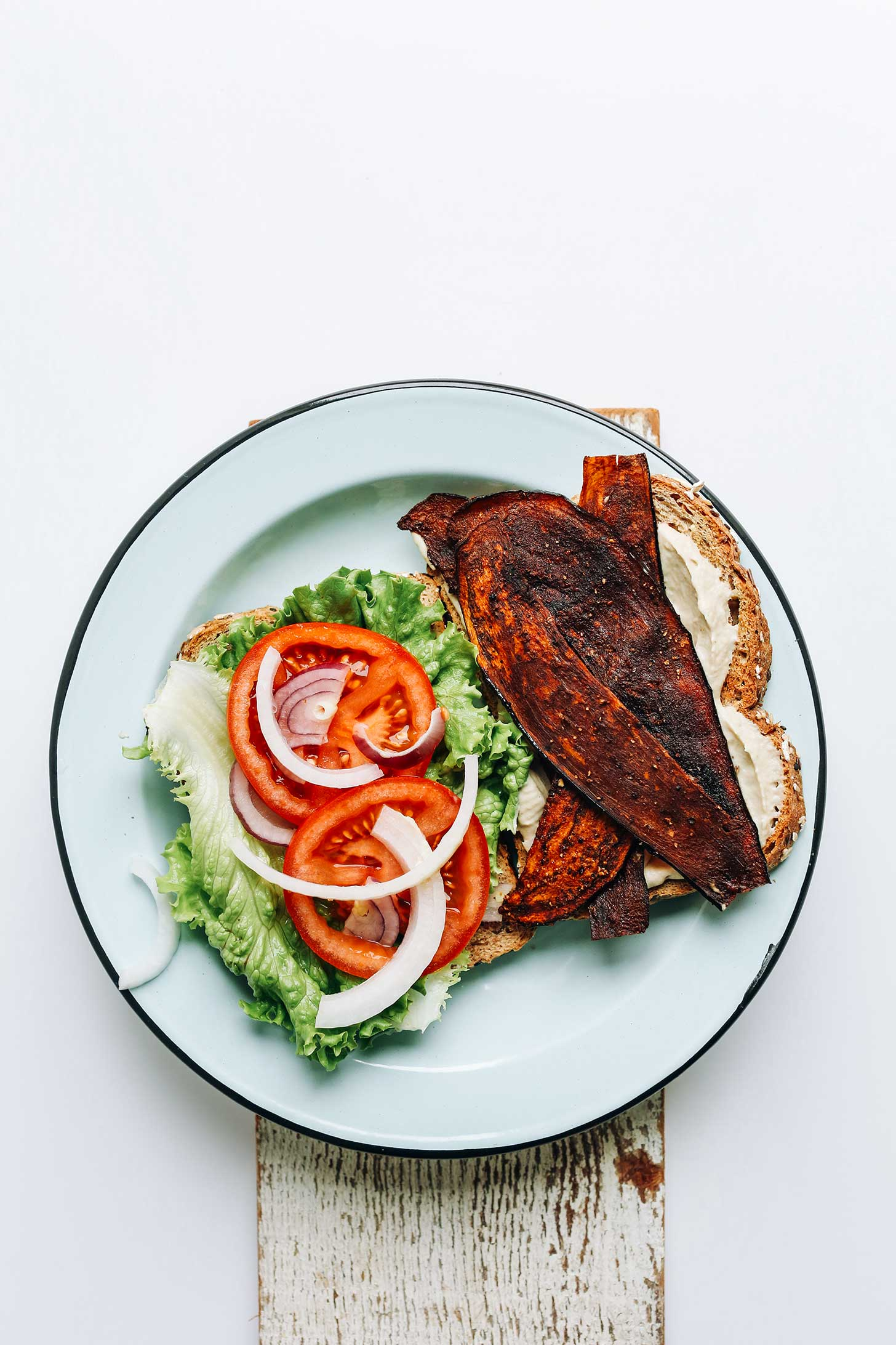 A plate with eggplant bacon, oil-free vegan mayo, sliced tomato, onion, and lettuce for a Vegan BLT