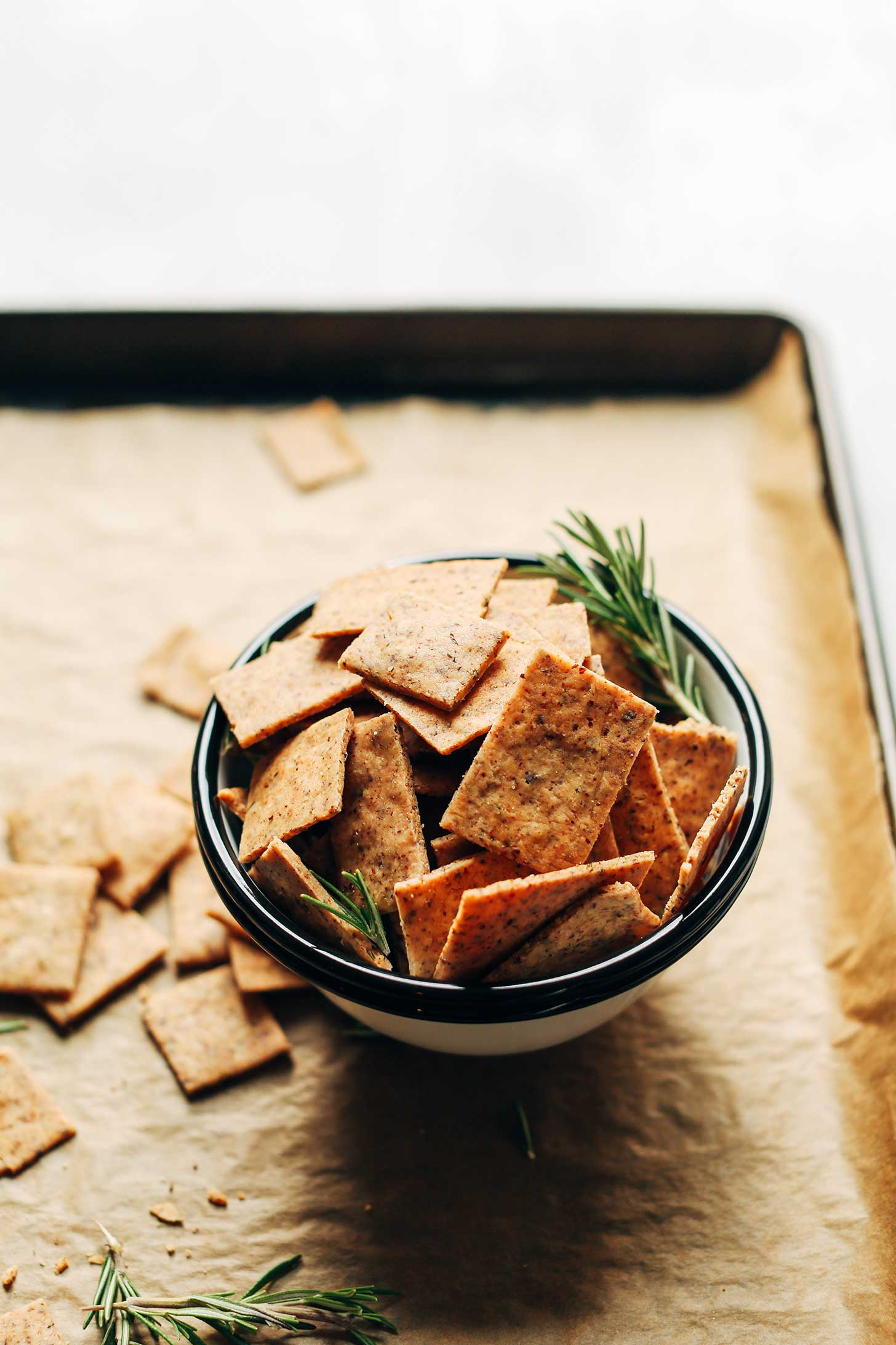 Close up shot of a bowl of Vegan Gluten-Free Crackers on a parchment-lined baking sheet