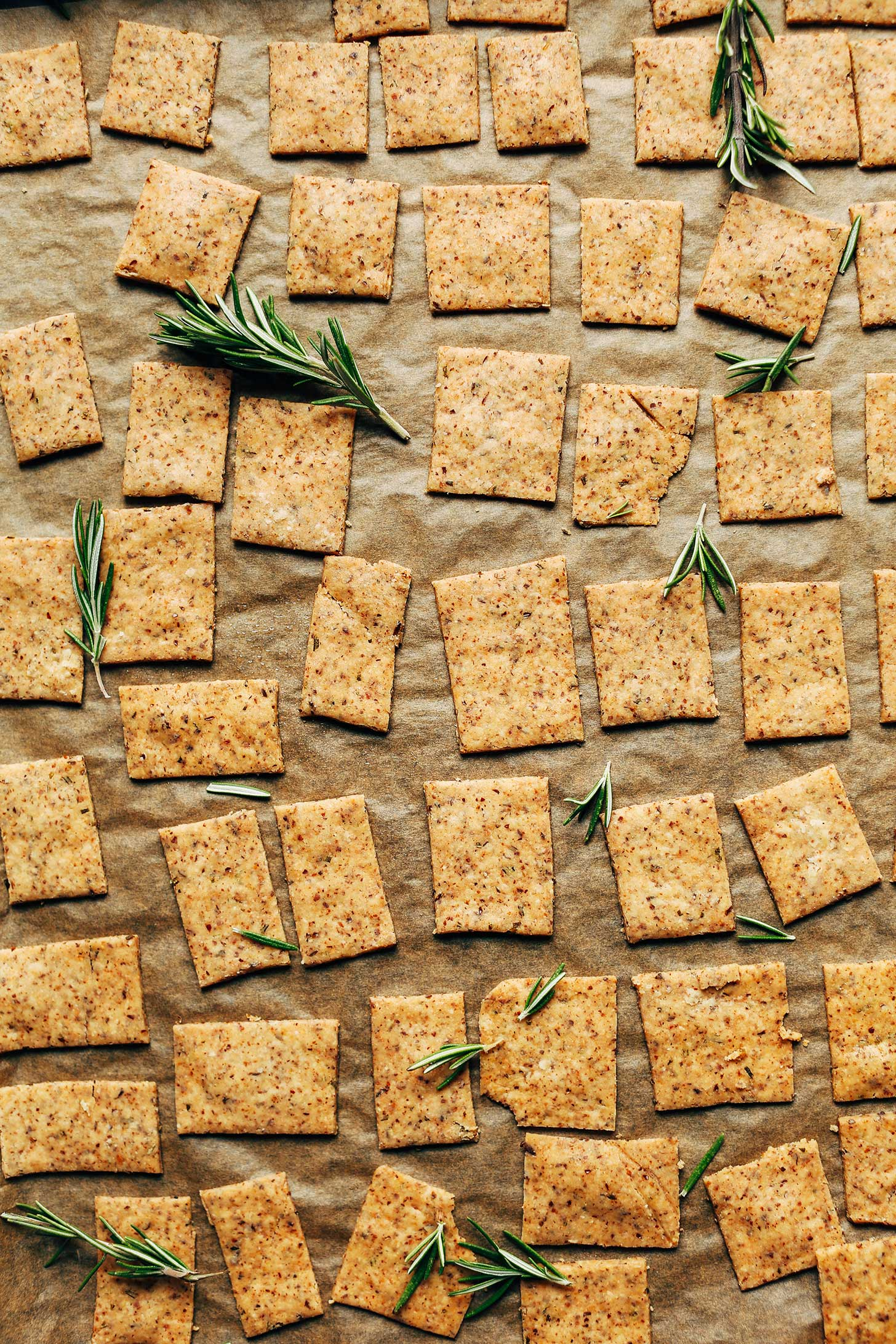 Baking sheet filled with crispy Gluten-Free Vegan Rosemary Crackers