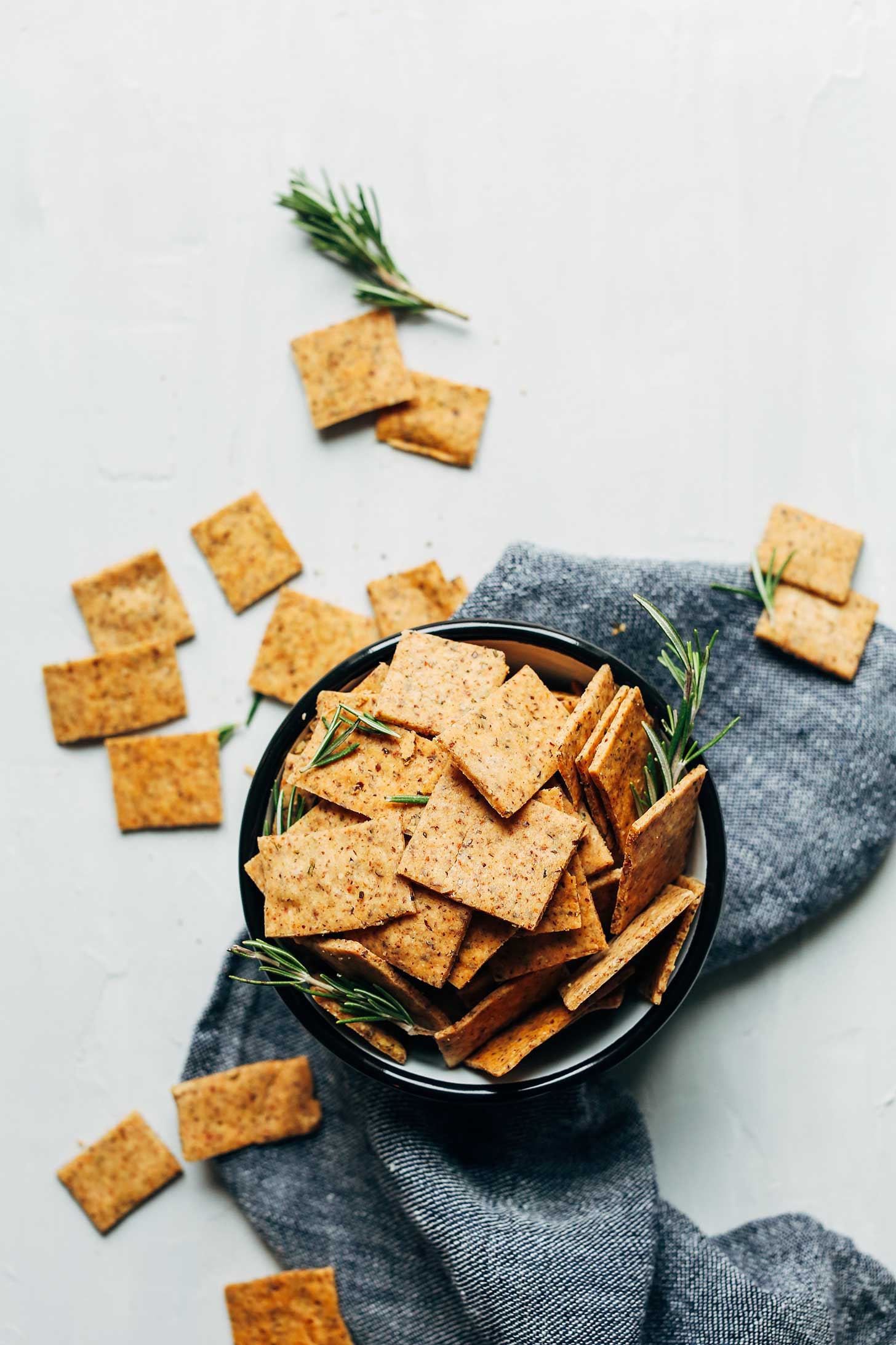 Bowl of crispy and delicious Vegan Gluten-Free Crackers with sprigs of rosemary