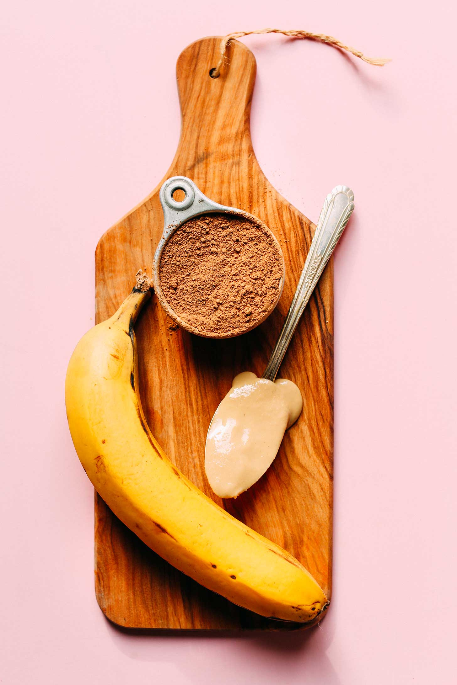 Cocoa powder, tahini, and banana on a wood board for making healthy Chocolate Tahini Banana Ice Cream