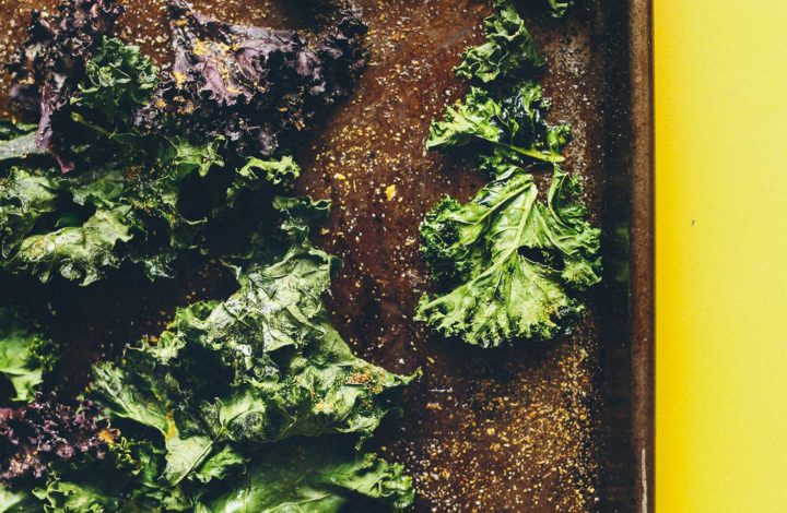 Baking sheet of homemade healthy kale chips for our tutorial on How to Make Kale Chips