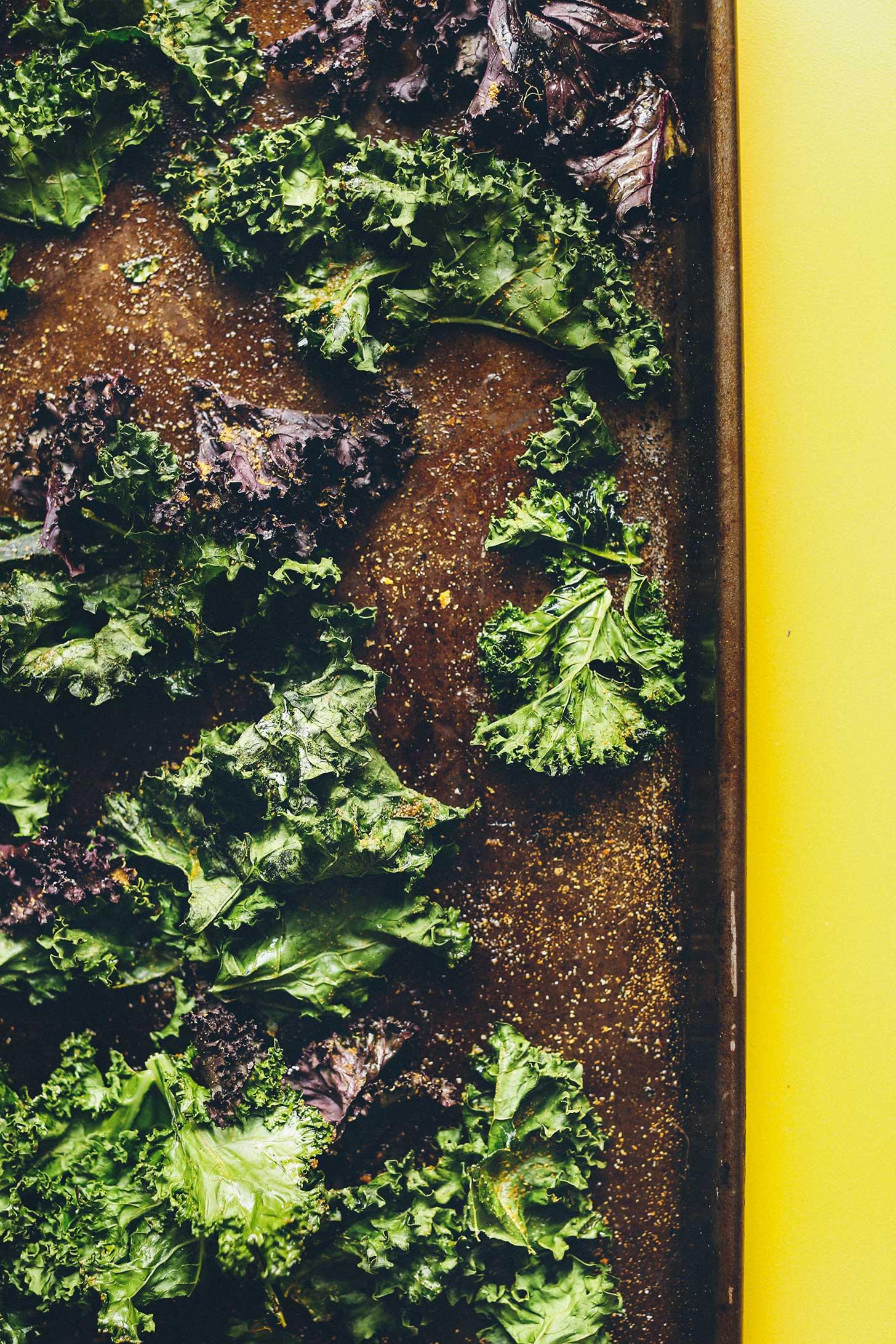 Perfectly crispy vegan kale chips on a baking sheet