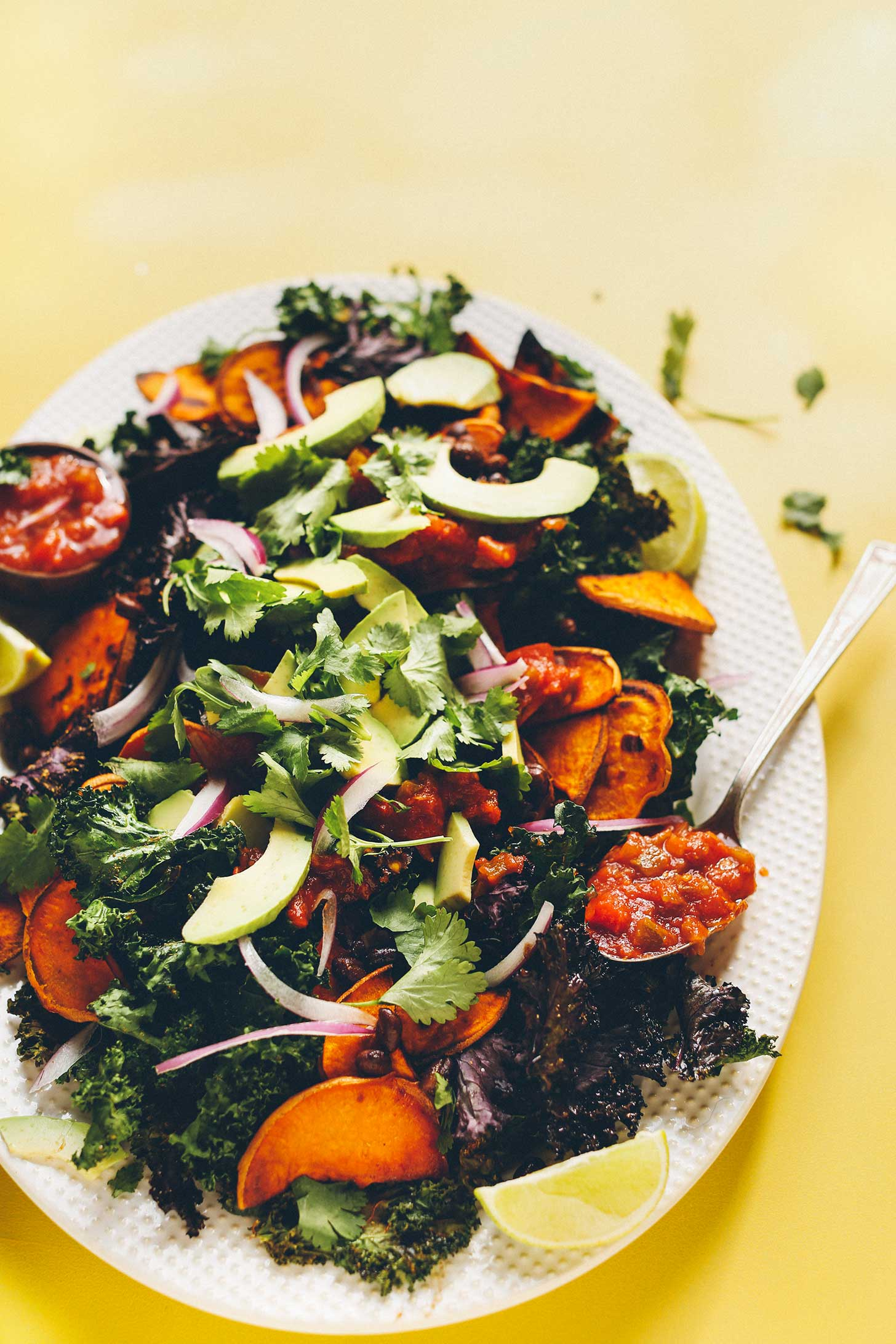 Big plate of plant-based Kale Nachos with Black Beans, Sweet Potatoes, Avocado, and salsa