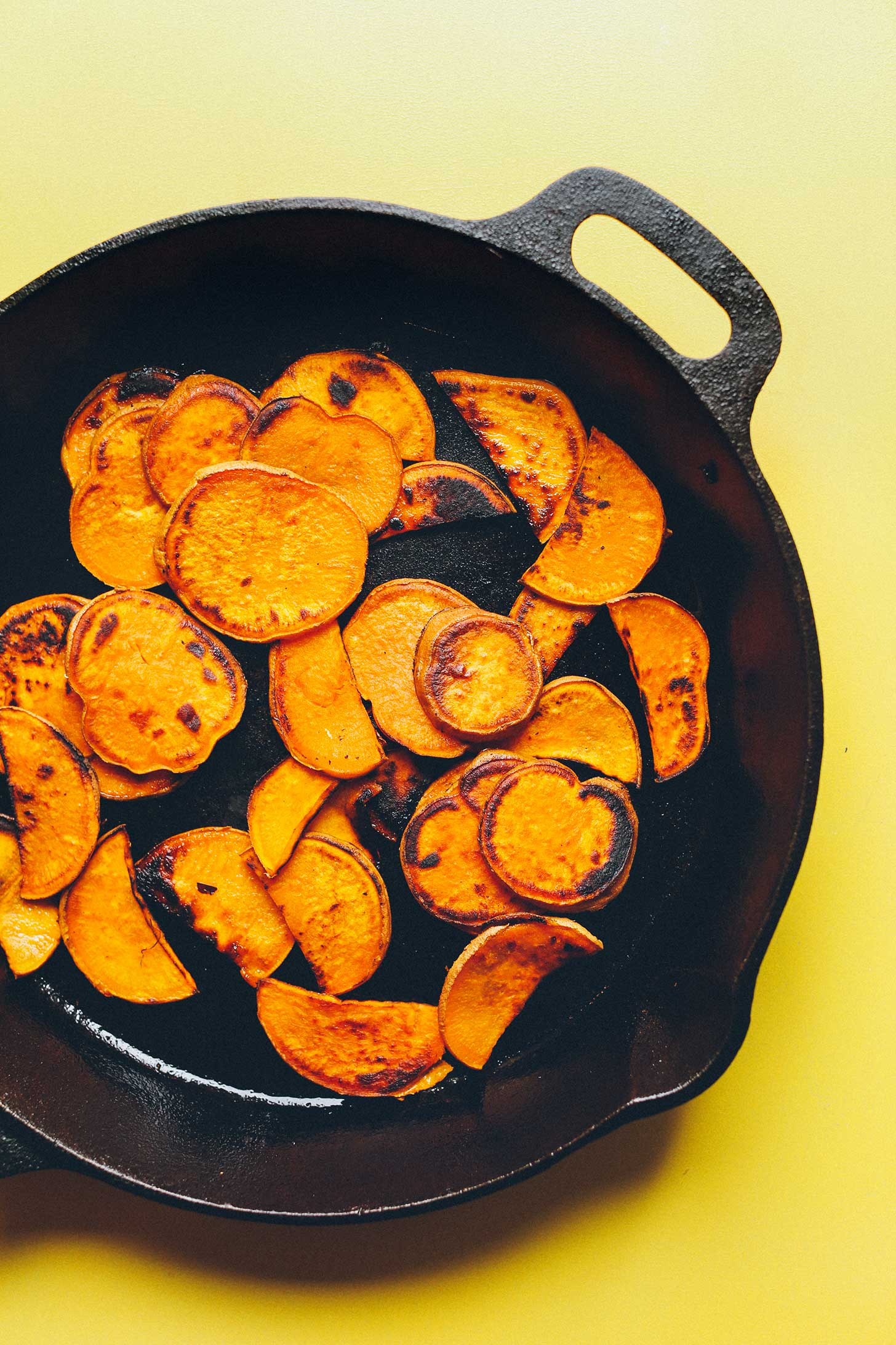 Cooking cast-iron skillet sweet potatoes for healthy plant-based kale nachos