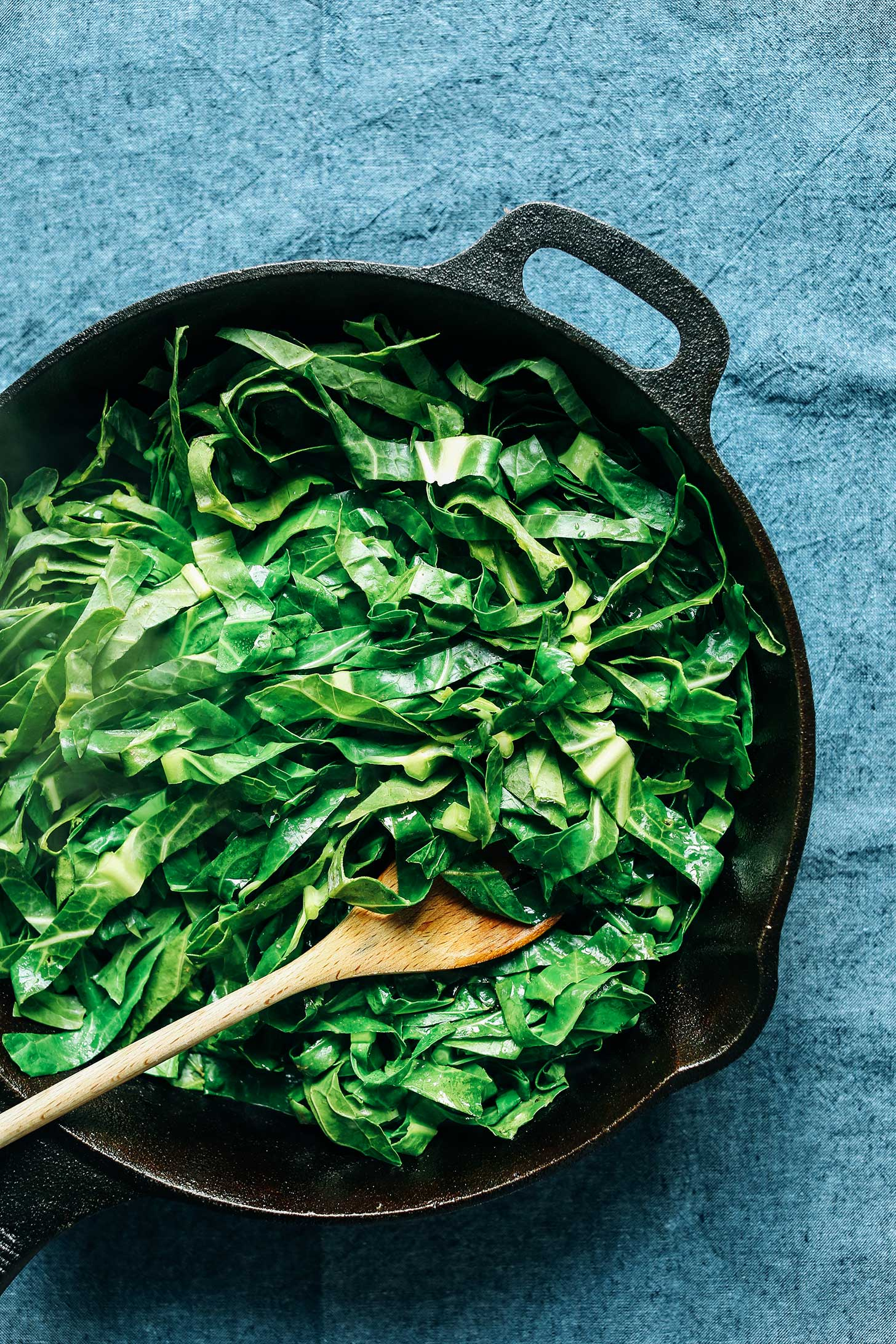 Cast iron skillet filled with a quick and easy vegan side dish of Collard Greens with Coconut Bacon