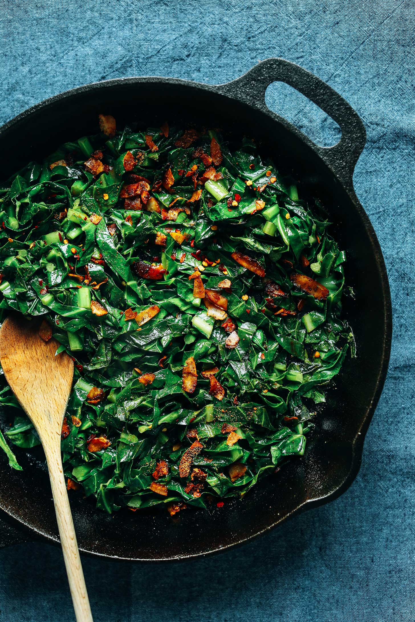 Using a wooden spoon to stir Collard Greens with Coconut Bacon in a cast iron skillet