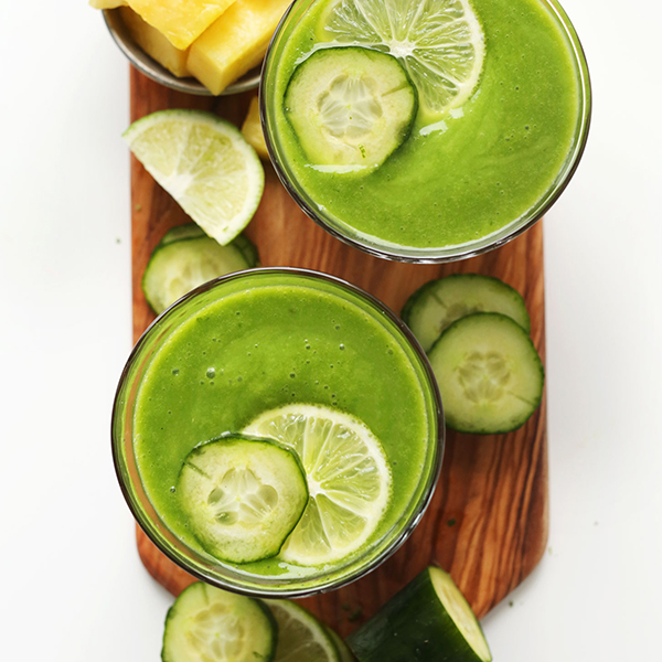 Cutting board with two glasses of our Creamy Vegan Cucumber Smoothie