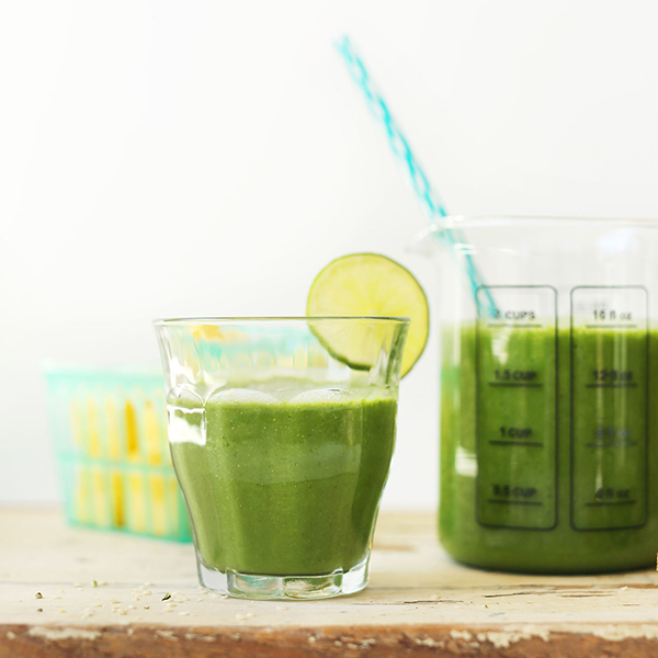 Measuring glass and drinking glass filled with our Ginger Green Smoothie recipe