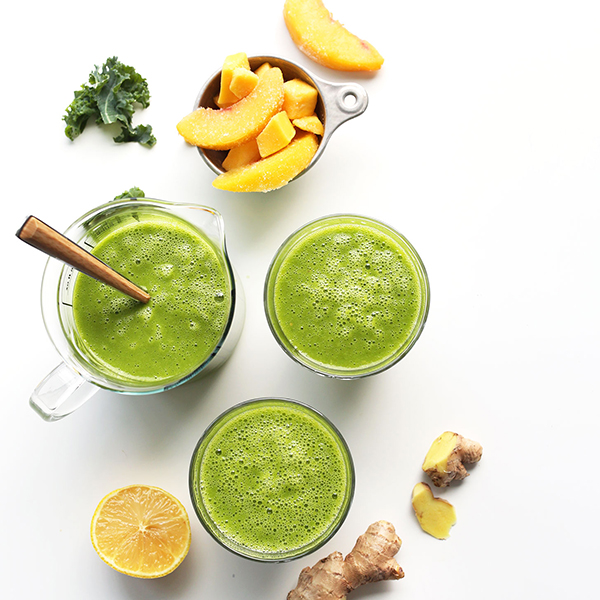 Measuring glass and glasses of our Mango Green Smoothie recipe beside ingredients to make it