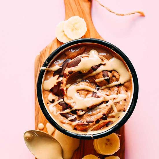 Banana slices around a bowl of Vegan Tahini Chocolate Soft Serve