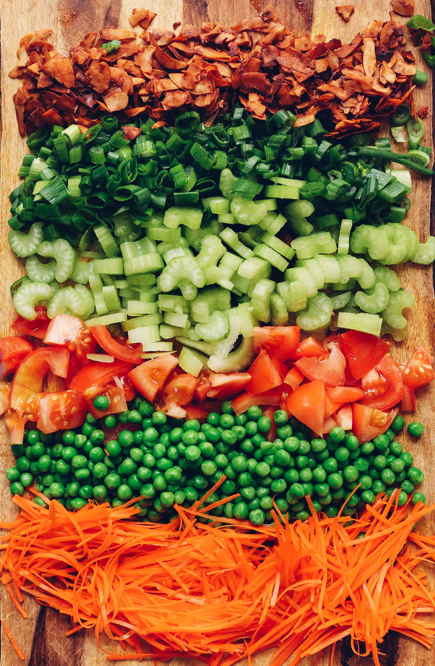 Shredded carrots, green peas, tomatoes, celery, green onion, and coconut bacon on a wood cutting board to be made into Vegan 7-Layer Salad