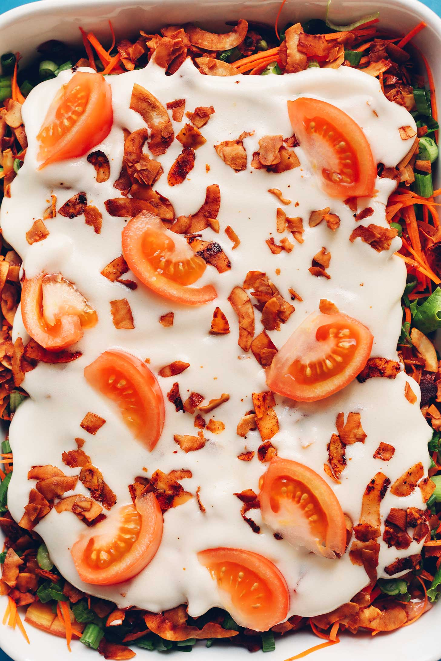 Ceramic dish full of Vegan 7-Layer Salad with a mayo, coconut bacon, and tomato top
