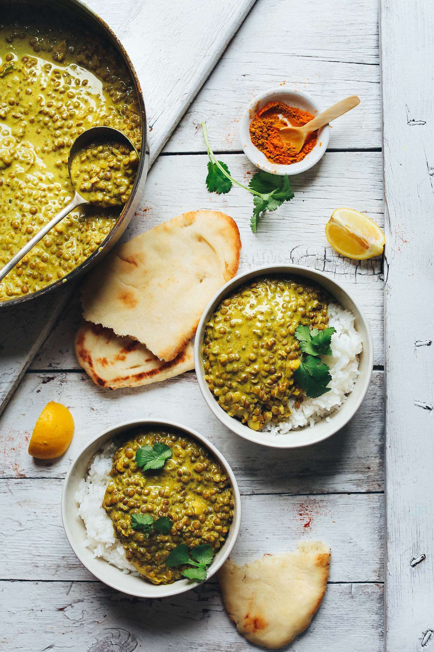 A pan and bowls of Vegan Lentil Dal alongside homemade Naan