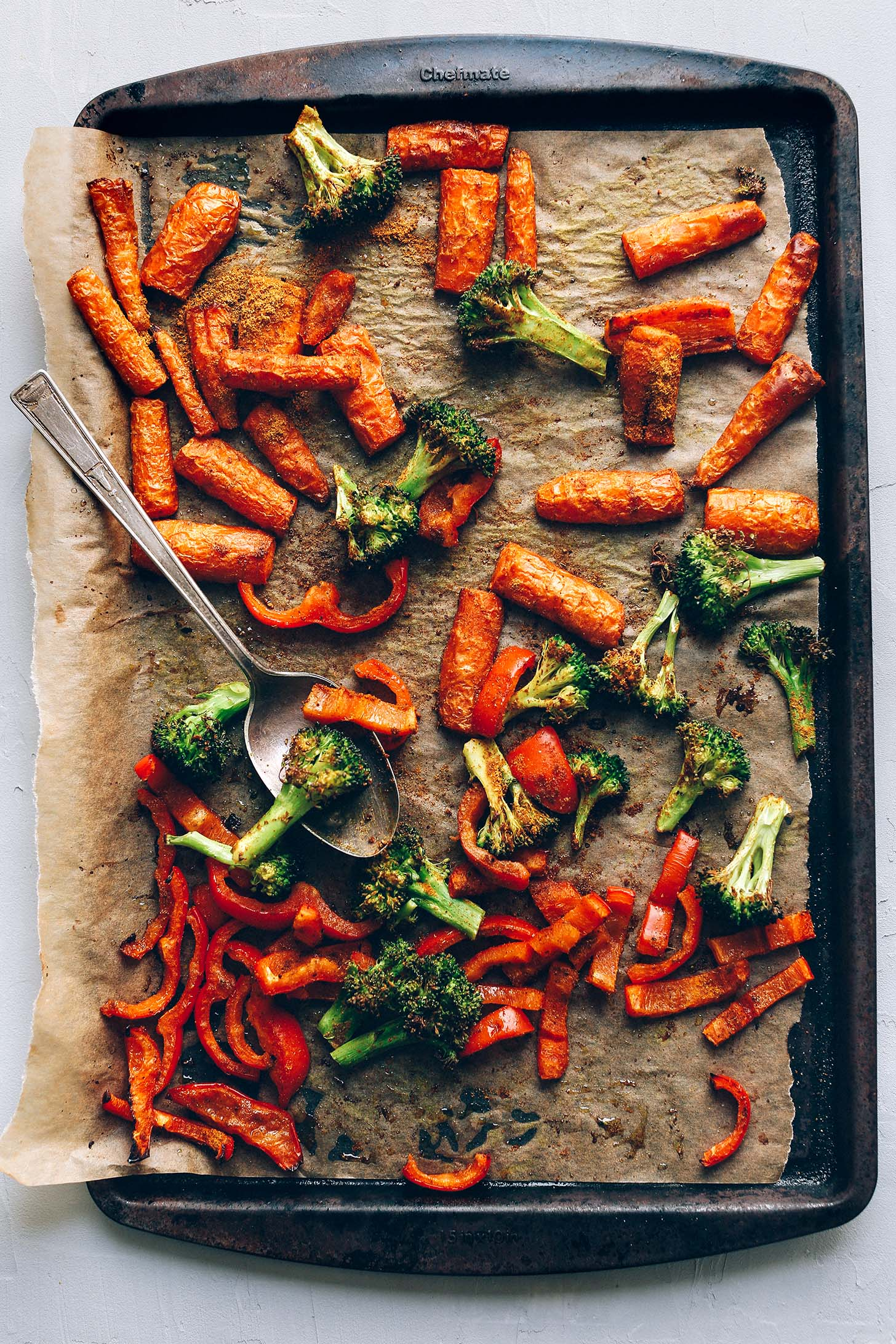 Parchment-lined baking sheet with roasted carrots and broccoli for a delicious Lentil Curry Salad recipe