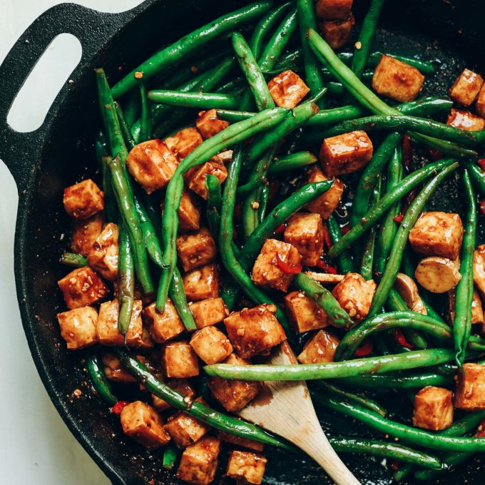 Using a wooden spoon to stir Almond Butter Tofu Stir-Fry in a cast iron skillet