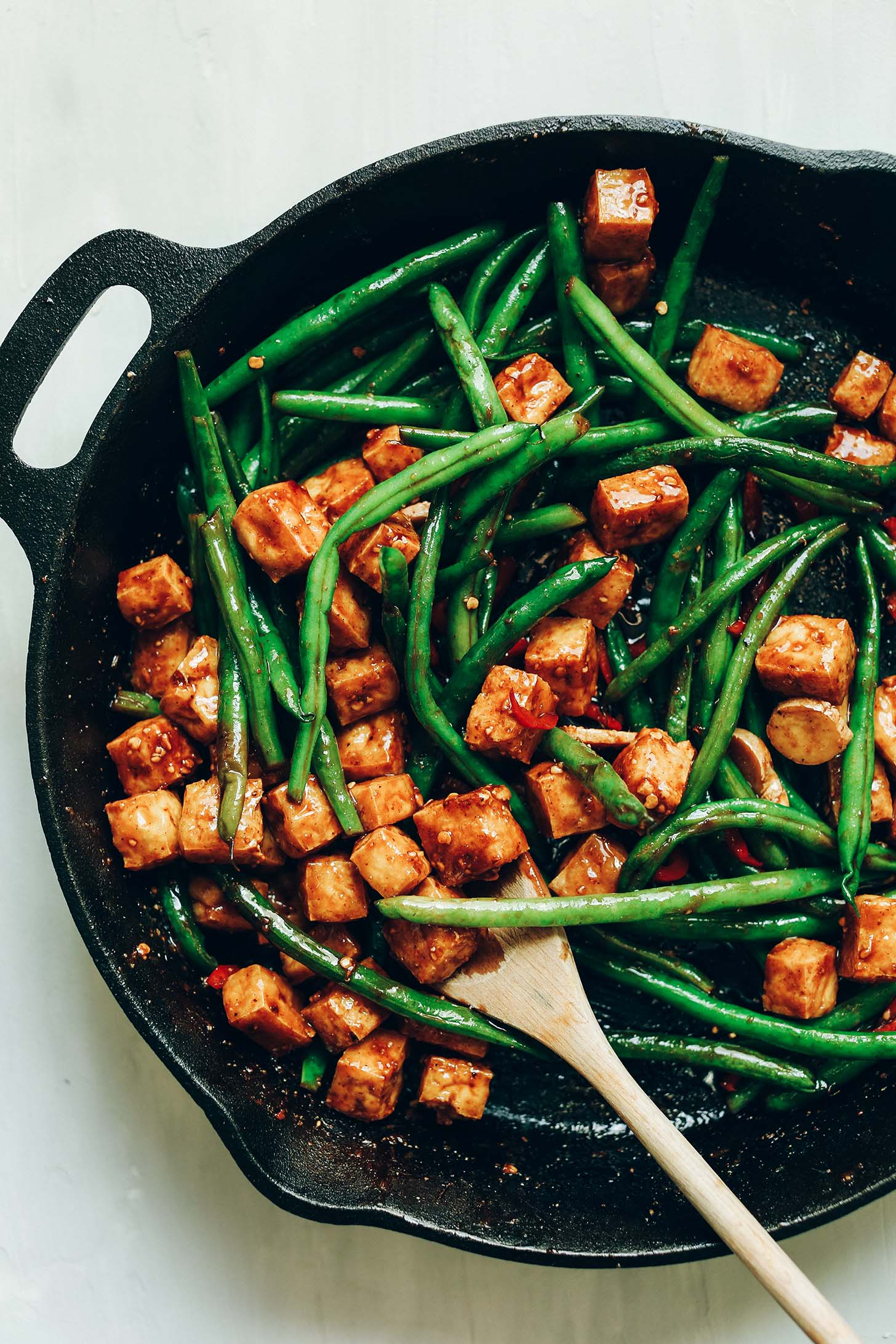 Cast iron skillet filled with green beans, tofu, and sauce for Almond Butter Tofu Stir-Fry