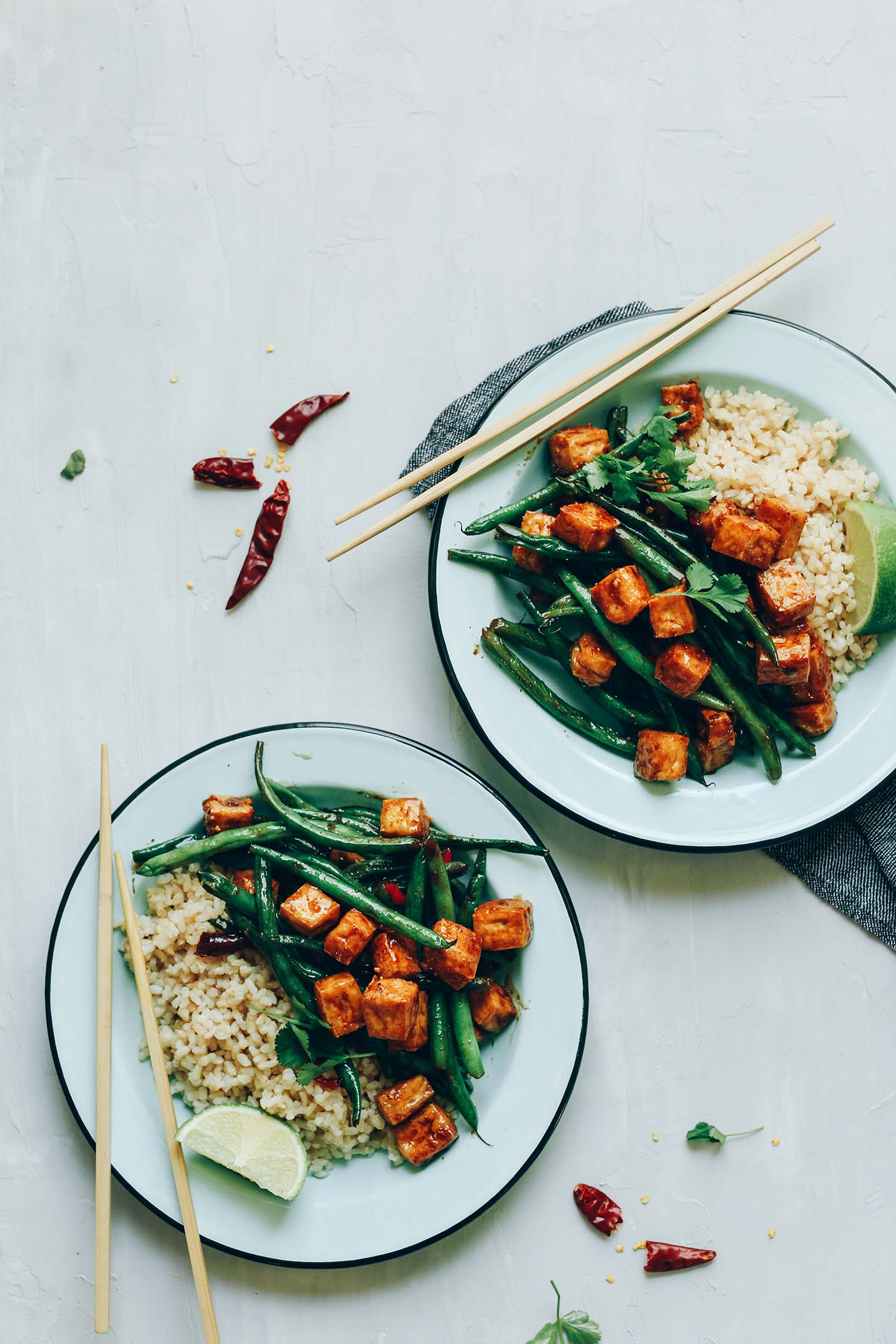 Two bowls of Almond Butter Tofu Stir-Fry with rice for a gluten-free vegan meal