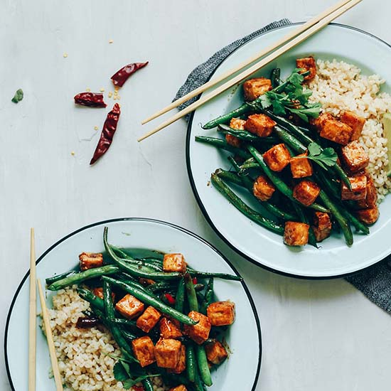 Two plates of our Almond Butter Tofu Stir Fry made with brown rice and green beans