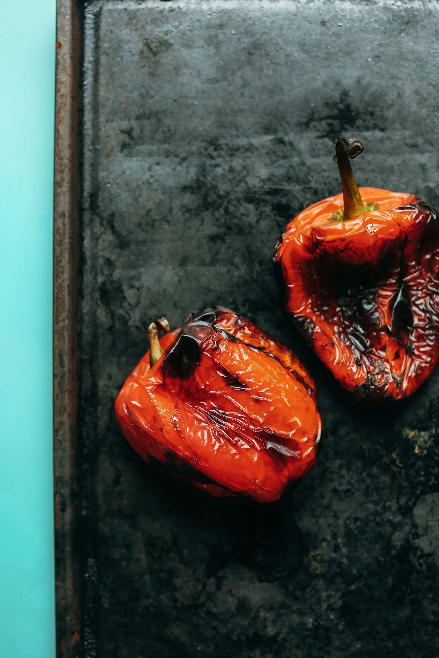 Roasting two red bell peppers on a baking sheet for Creamy Vegan Roasted Red Pepper Tomato Soup