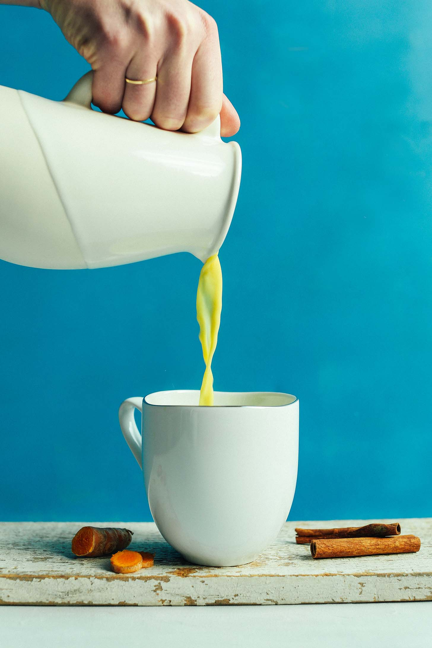 Pouring Creamy Golden Milk into a mug to be enjoyed as an anti-inflammatory boost