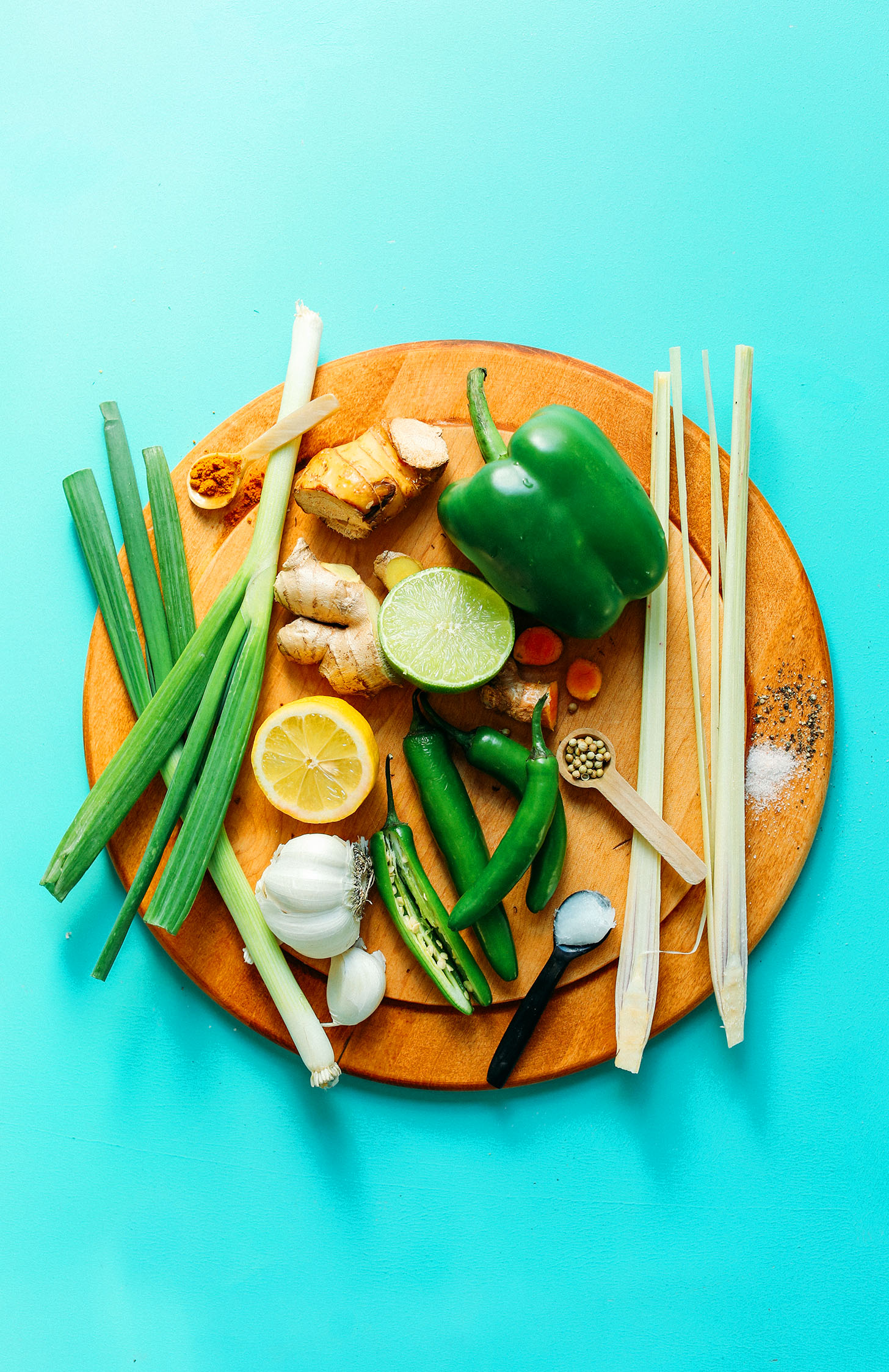 Wood cutting board with lemongrass, green bell pepper, lime, turmeric, galangal, ginger, lemon, serranos, garlic, green onion, salt, and spices for homemade easy green curry paste