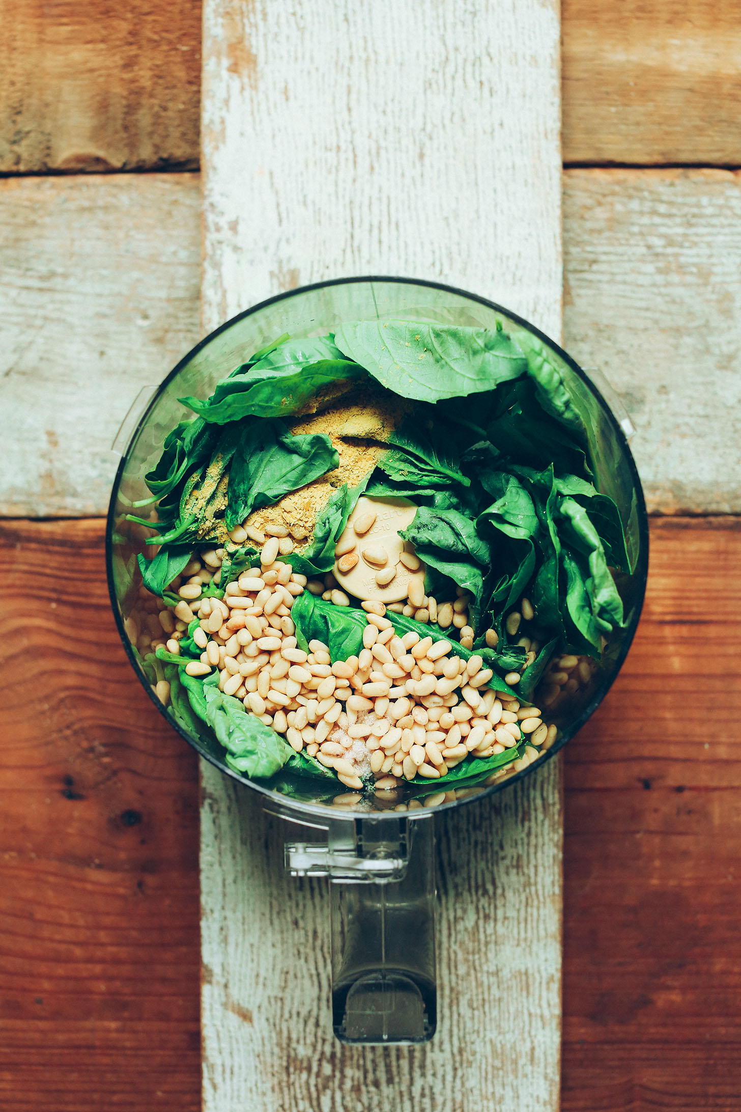 Food processor filled with ingredients for making homemade gluten-free vegan basil pesto