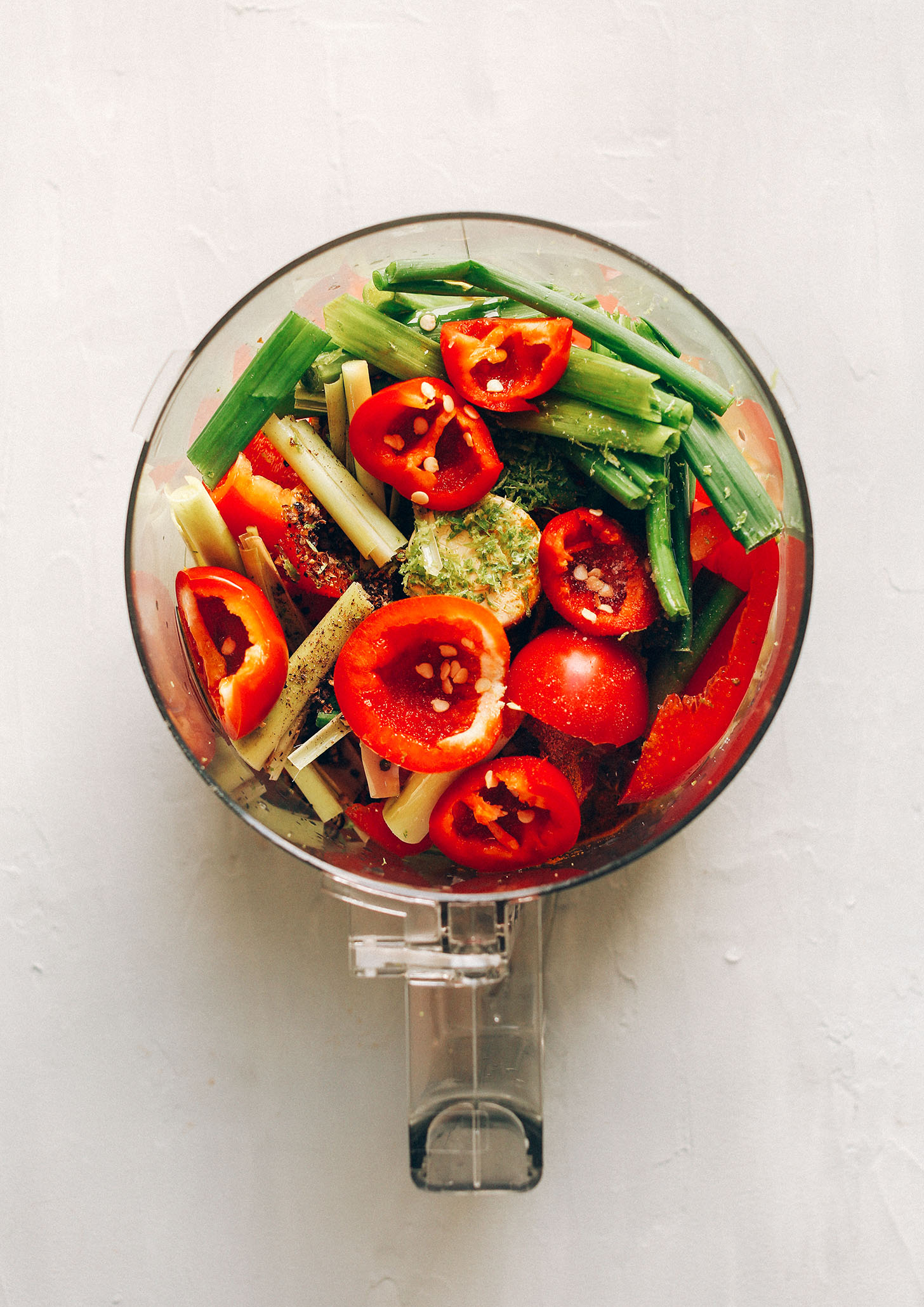Food processor filled with ingredients for our gluten-free vegan Red Curry Paste recipe