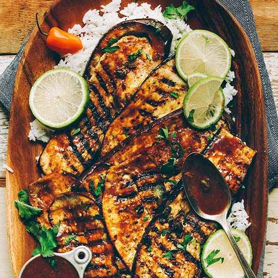 Wood platter filled with Vegan Jerk Eggplant slices over white rice