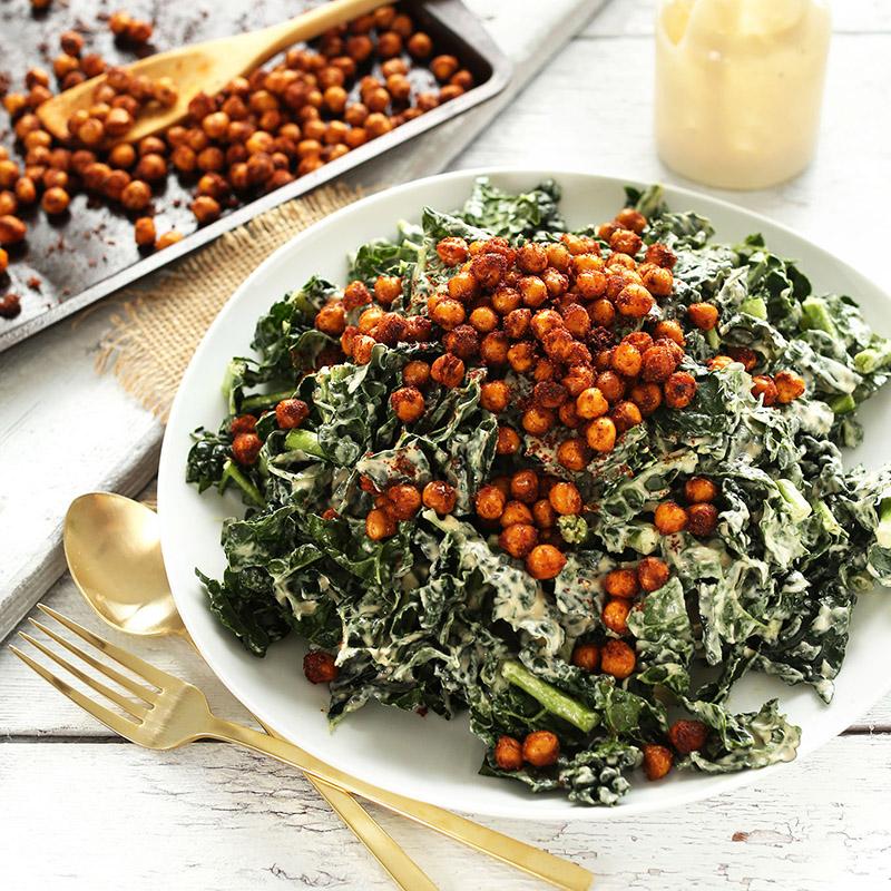 Big plate of Garlicky Kale Salad beside a baking sheet of Crispy Chickpeas