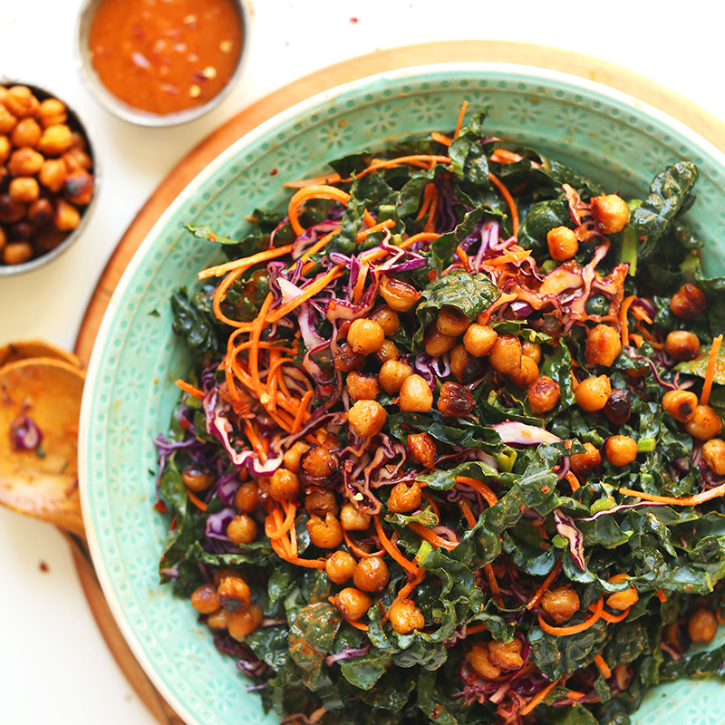 Bowl of Asian Kale Salad with Crispy Miso Chickpeas and measuring cups of extra dressing and chickpeas on the side