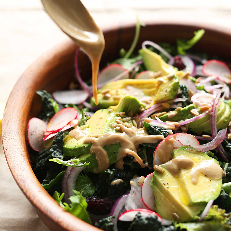 Drizzling Tahini Dressing onto a big bowl of our Detox Salad recipe