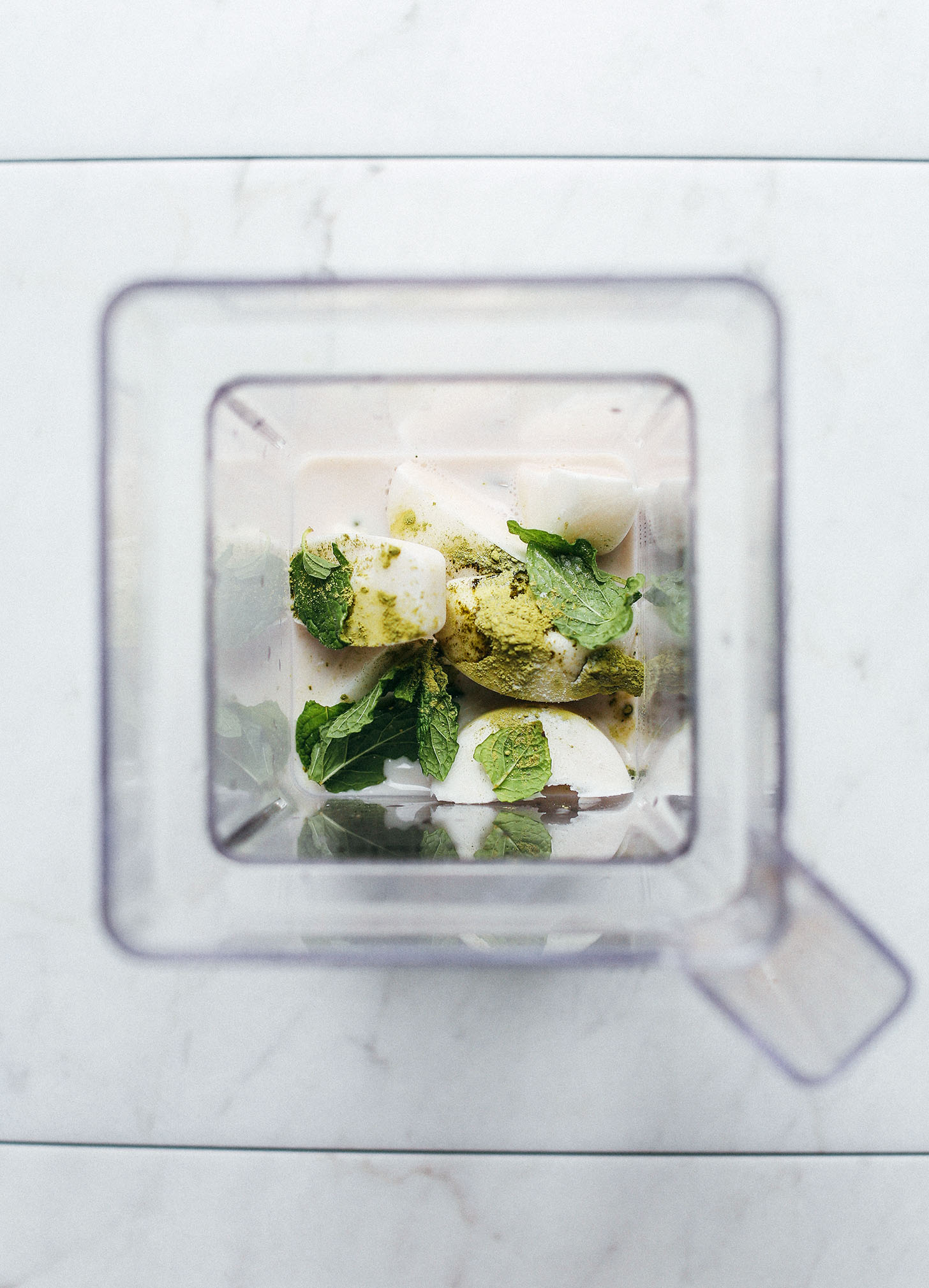 Blender with ingredients for making our Vegan Mint Matcha Shamrock Shake recipe