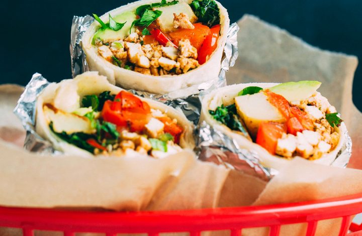 Three healthy Vegan Breakfast Burritos in a red basket