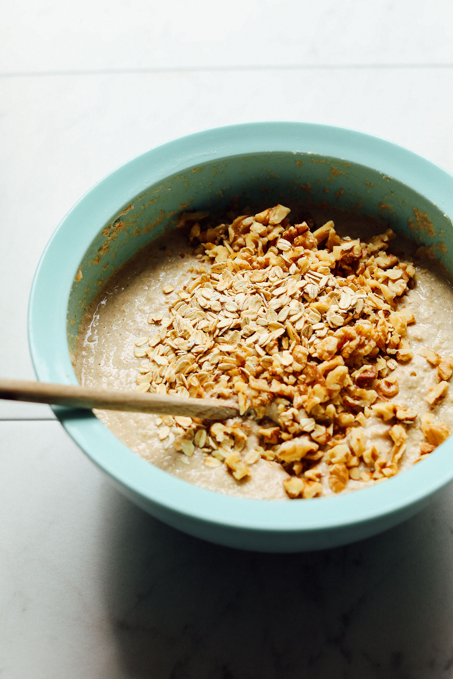 Stirring oats and walnuts into gluten-free Banana Pancakes batter
