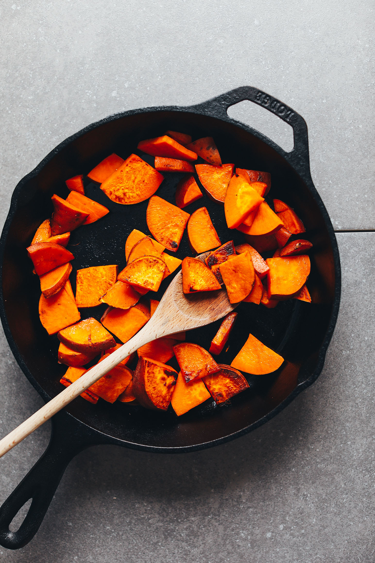 Browning sweet potatoes in a cast iron skillet for Vegan Breakfast Salad