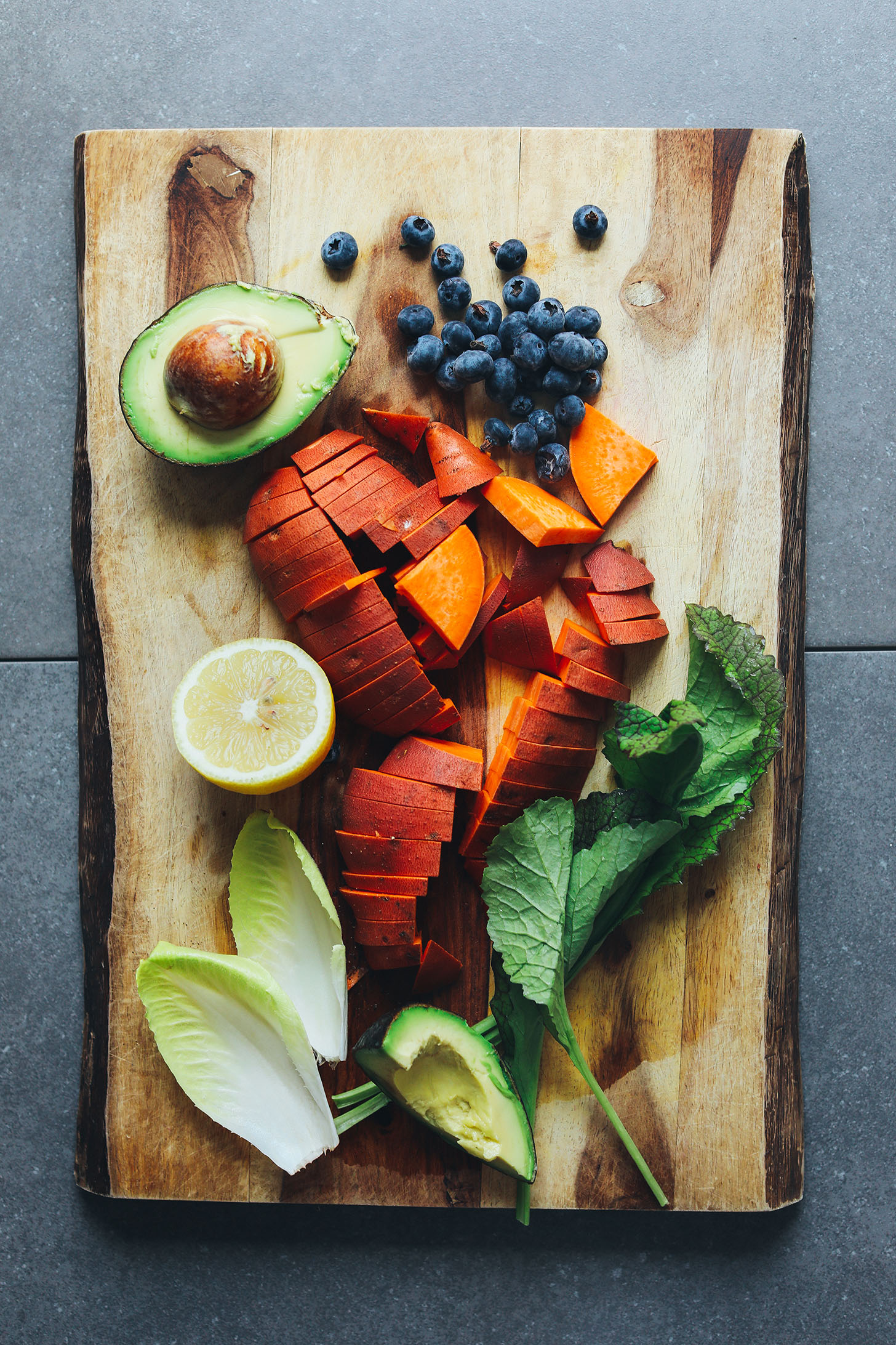 Wood cutting board featuring avocado, blueberries, sweet potato, lemon, endive, and mustard greens for a Vegan Breakfast Salad
