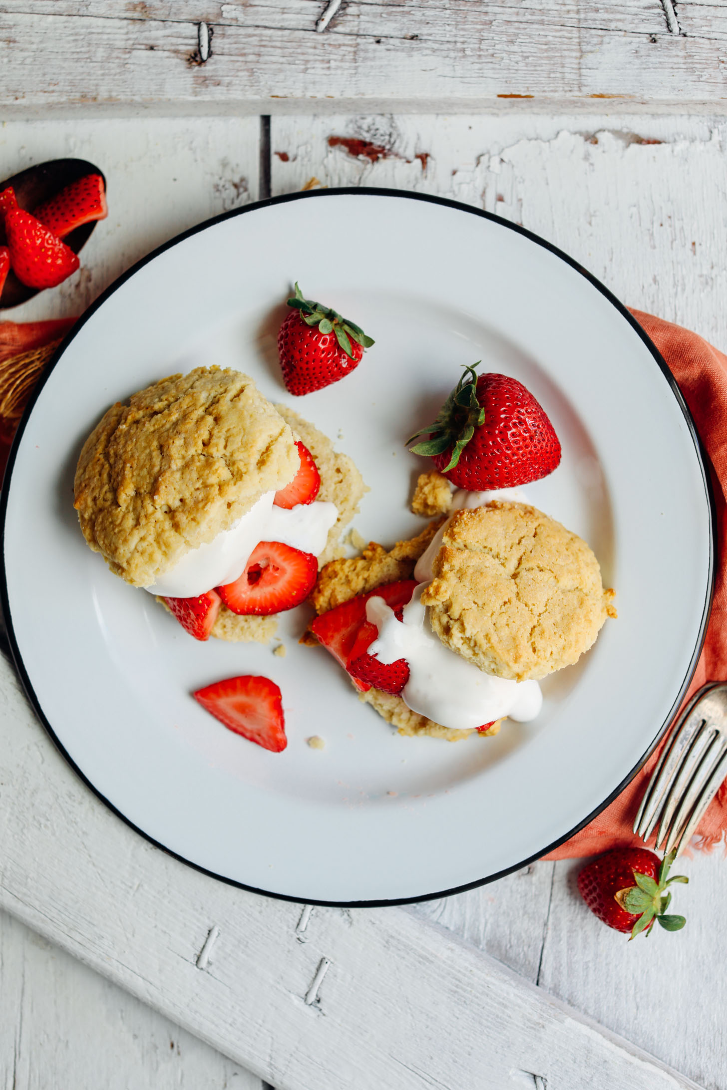 Top down photo showing perfectly browned vegan shortcake biscuits stuffed with fresh strawberries and coconut whipped cream
