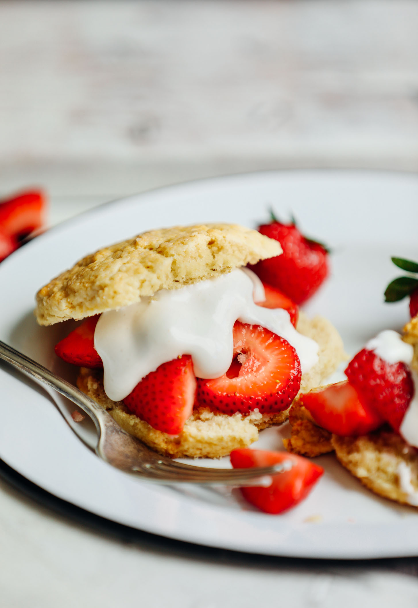 Plate with a vegan gluten-free shortcake biscuit with fresh strawberries and coconut whipped cream