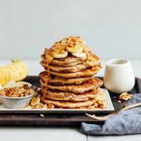 Platter with a stack of Banana Pancakes topped with banana slices, peanut butter, and granola