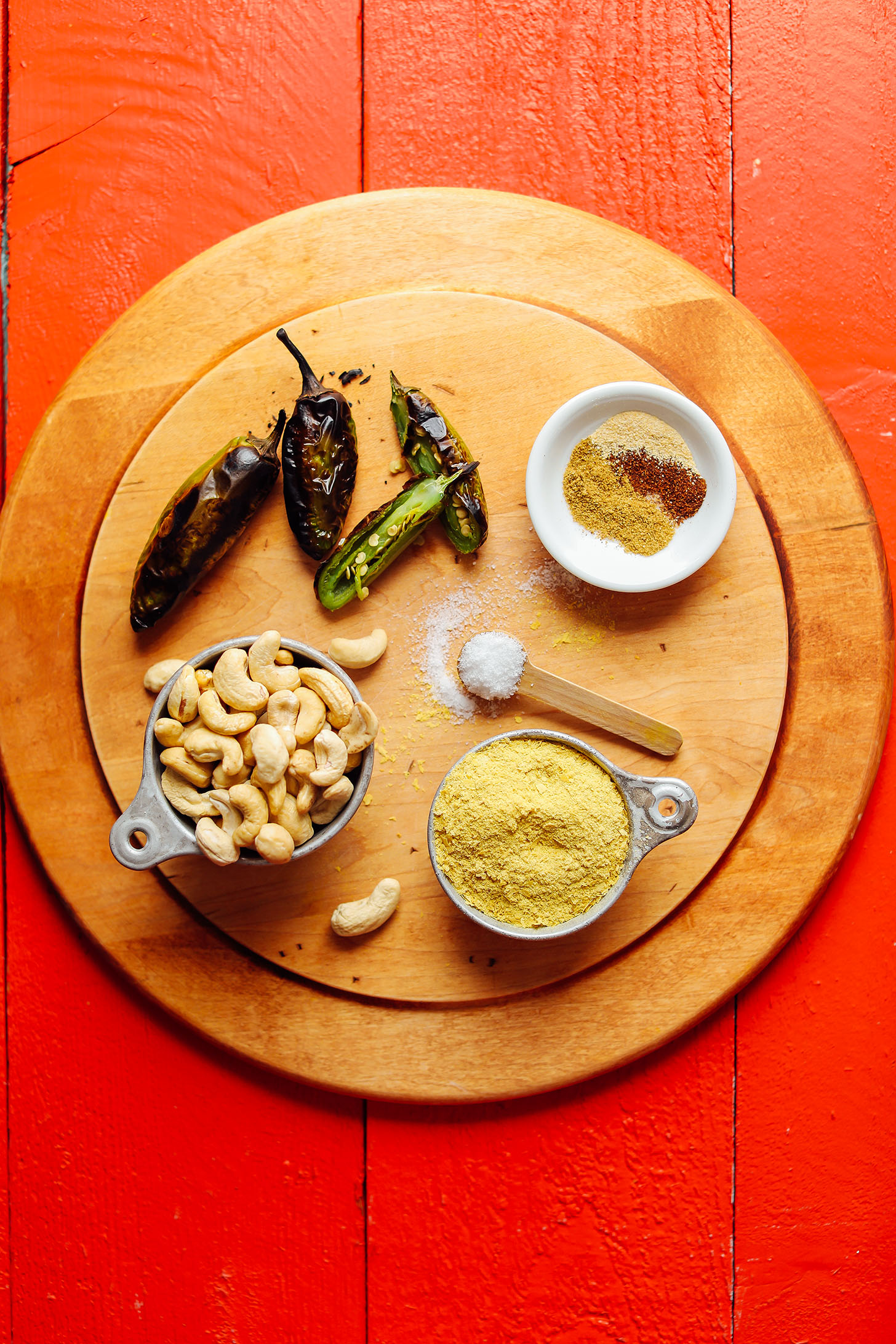 Wood cutting board with roasted jalapenos, cashews, nutritional yeast, salt, and spices for Creamy Roasted Jalapeno Vegan Queso