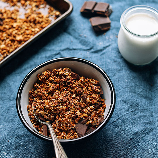 Bowl and tray of Chocolate Sea Salt Granola beside a small jar of dairy-free milk