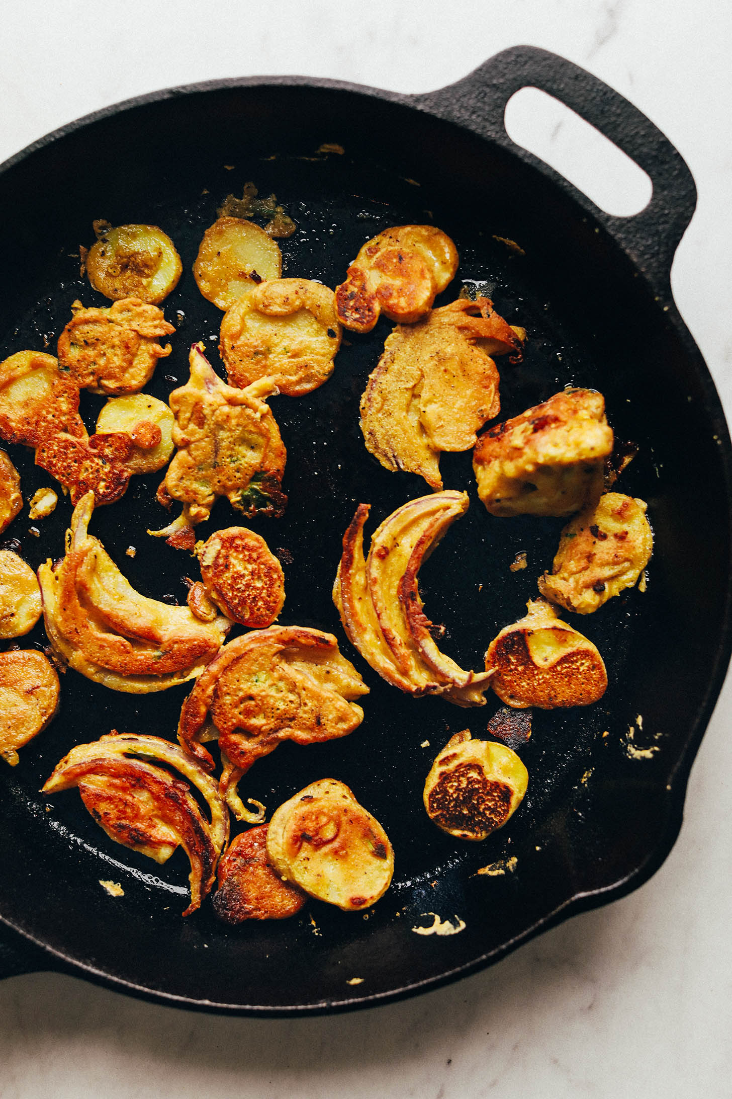 Pan frying Vegetable Pakoras in a cast-iron skillet