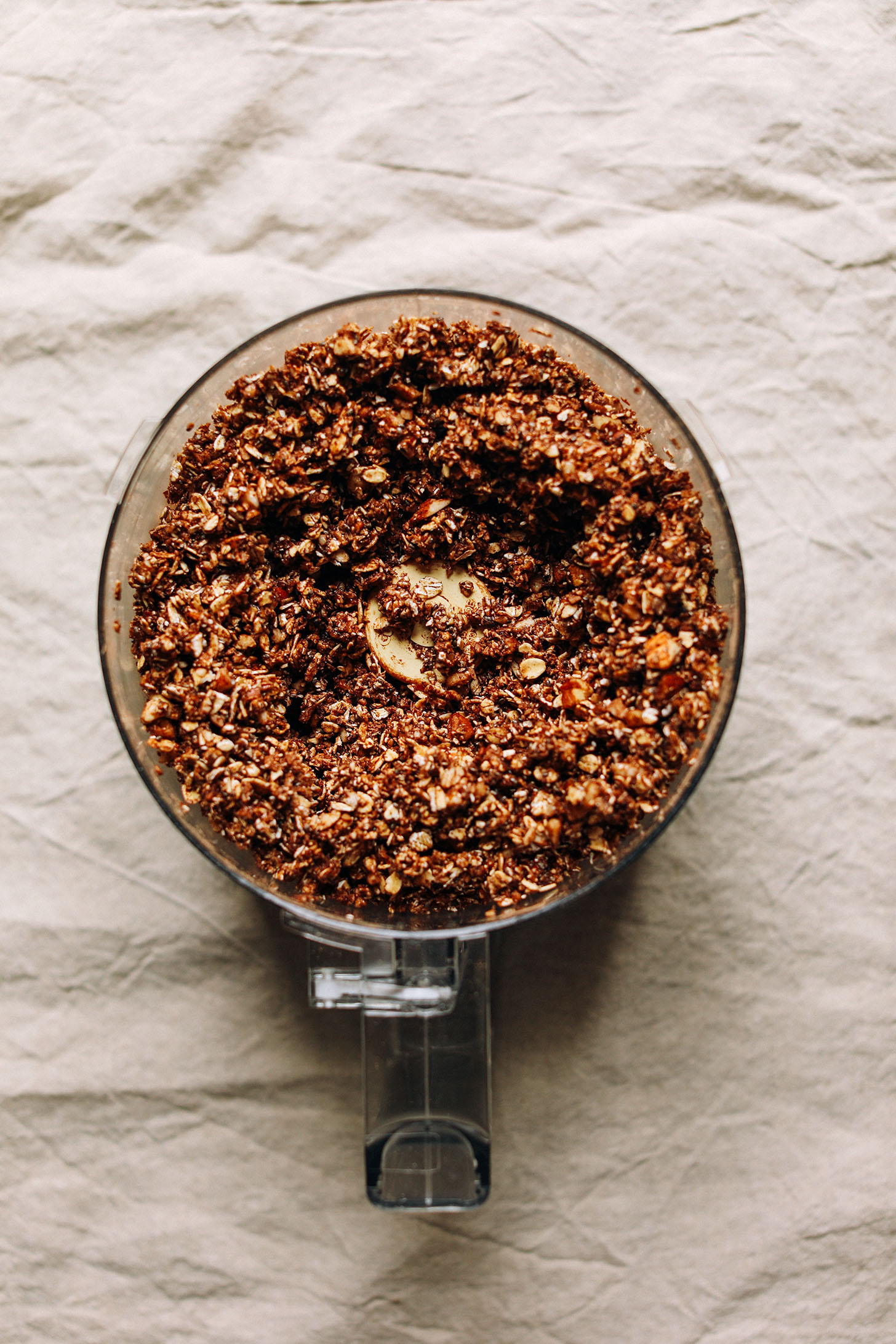 Food processor with freshly blended ingredients for Dark Chocolate Granola with sea salt