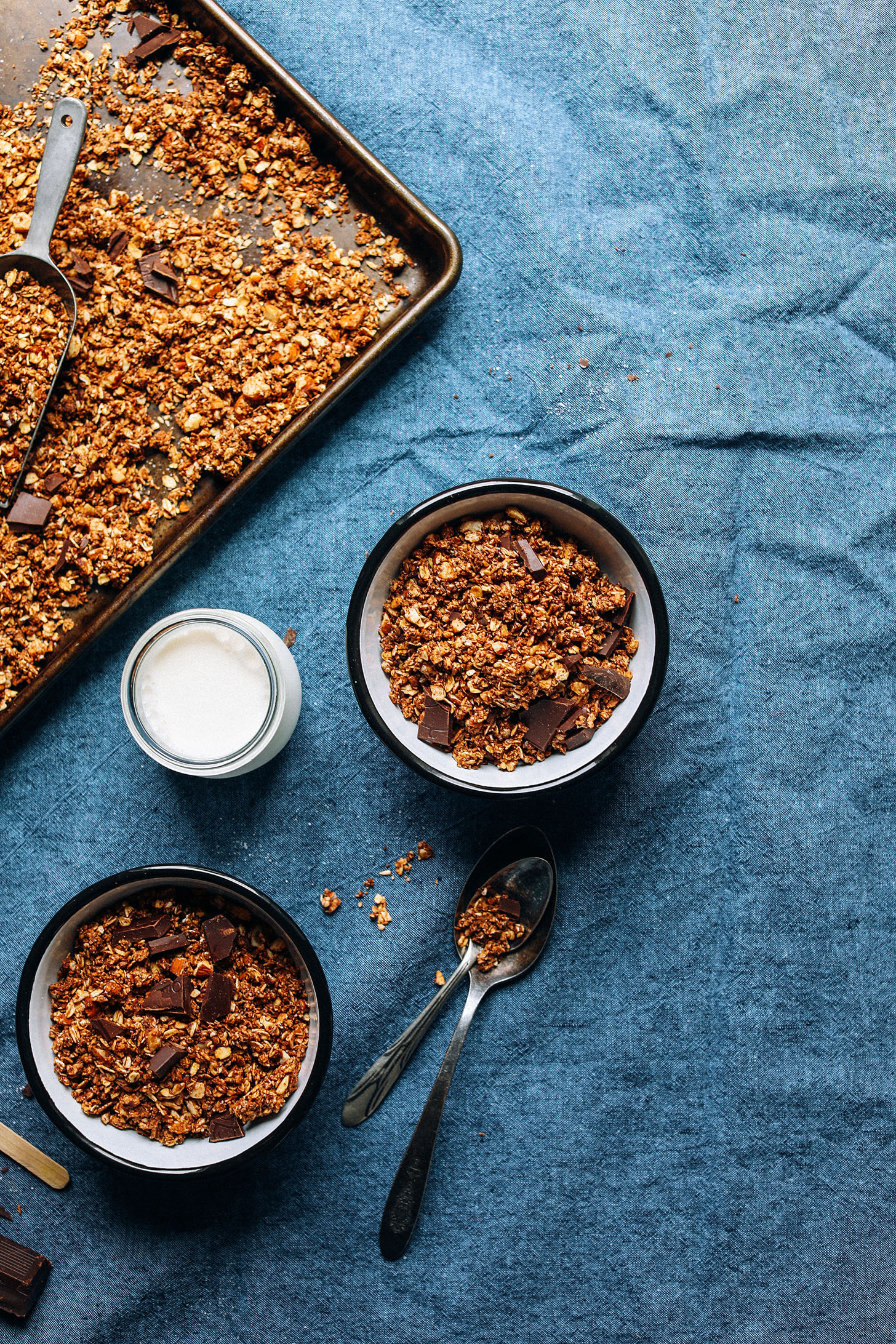Baking sheet and two serving bowls with gluten-free vegan Dark Chocolate Granola with sea salt