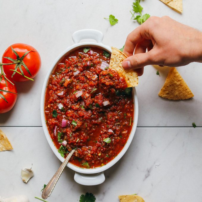Scooping up our Perfect Red Salsa recipe with a tortilla chip