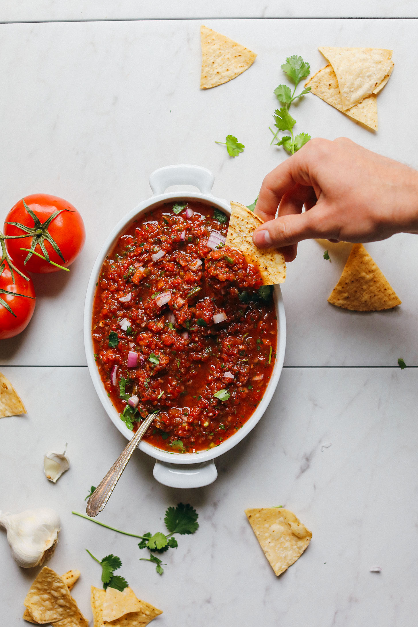 Dipping a tortilla chip into a bowl of our Perfect Red Salsa recipe